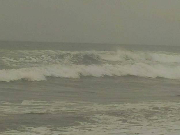 Samar-samar tampak orang bermain surfing di kejauhan
