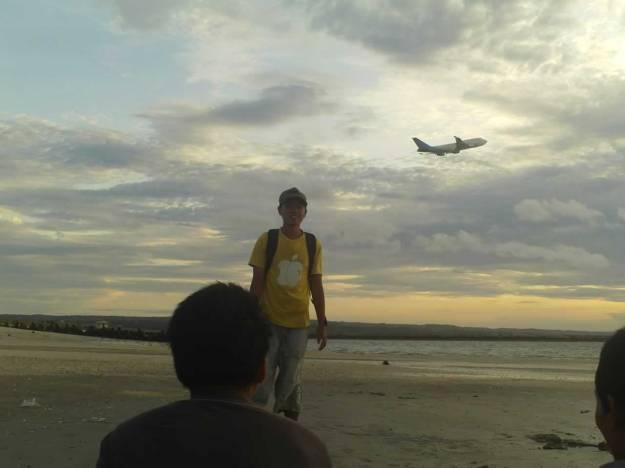 Pesawat lepas landas di atas pantai Kuta