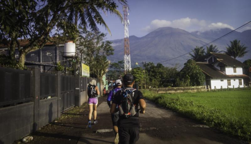Berlari di kampung. Gunung Guntur tampak di kejauhan.