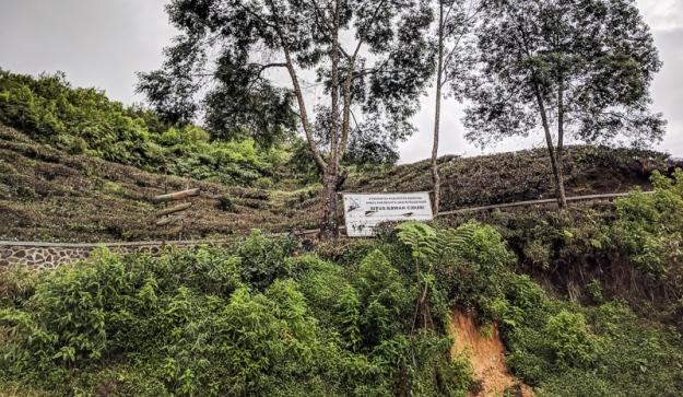"""Papan tulisan """"Situs Kawah Cibuni"""" di pinggir jalan"""